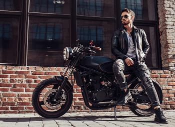 Man leans against motorcycle in front of a brick building
